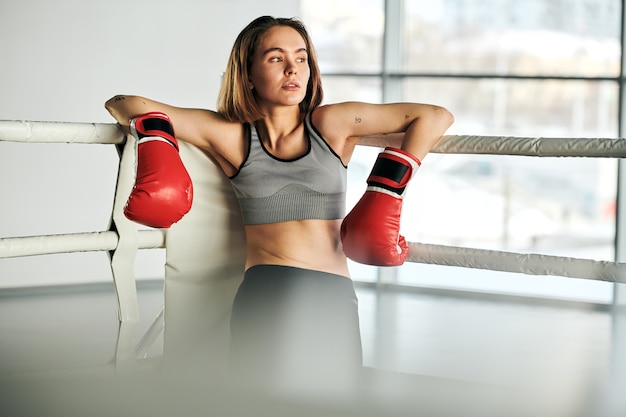 Junge blonde frau in den roten boxhandschuhen und im trainingsanzug, die durch fenster schauen, während durch die stangen der sportbahn nach dem training stehen
