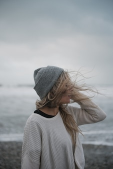 Junge blonde frau in der depression mit einem hut, der auf dem strand in einem windigen wetter geht
