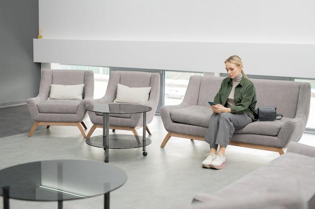 Junge blonde frau in der freizeitkleidung, die auf couch innerhalb des zeitgenössischen medizinischen zentrums sitzt und telefon benutzt, während sie auf ihren zug wartet