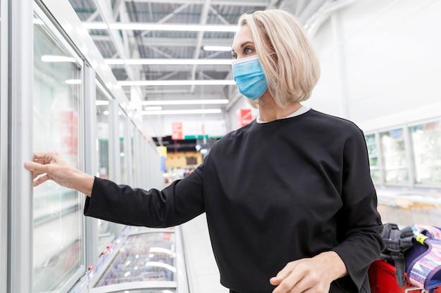 Junge blonde frau in der maske in einem supermarkt. coronavirus pandemie.