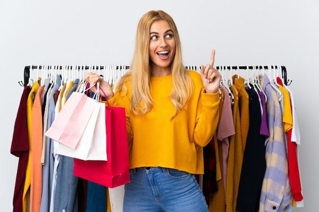 Junge blonde frau in einem bekleidungsgeschäft und hält einkaufstaschen, die beabsichtigen, die lösung zu realisieren, während sie einen finger anheben