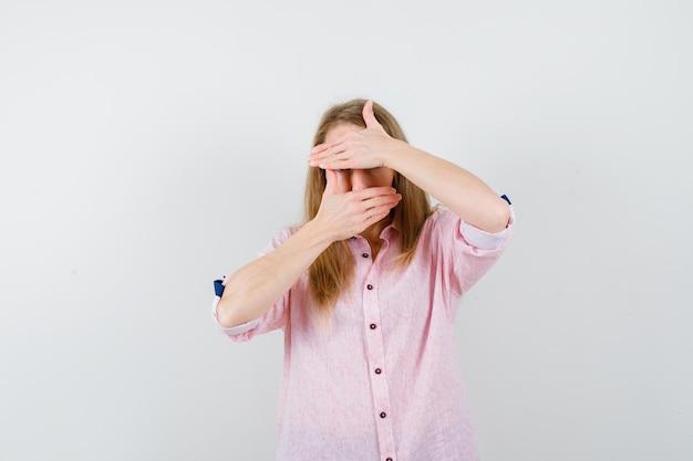 Junge blonde frau in einem lässigen rosa hemd, das ihr gesicht bedeckt