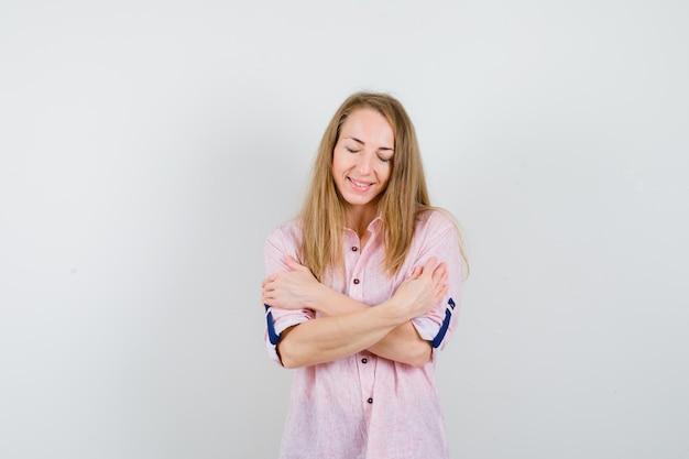 Junge blonde frau in einem lässigen rosa hemd