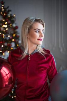 Junge blonde frau in einem roten trainingsanzug auf weihnachtsdekorationen