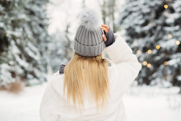 Junge blonde frau in einem weißen kittel mit blick auf den winterwald