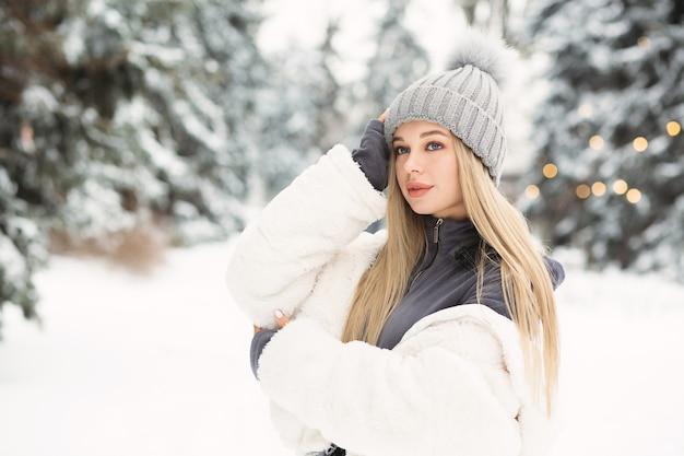 Junge blonde frau in einem weißen mantel, die in den winterwald geht. platz für text