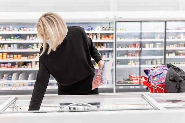 Junge blonde frau in einer medizinischen maske im supermarkt wählt produkte. coronavirus pandemie.