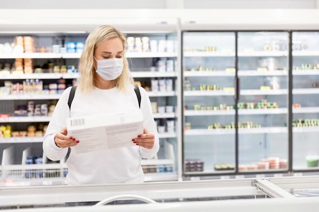 Junge blonde frau in einer medizinischen maske in einem supermarkt in der tiefkühlabteilung