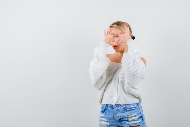 Junge blonde frau in einer weißen strickjacke