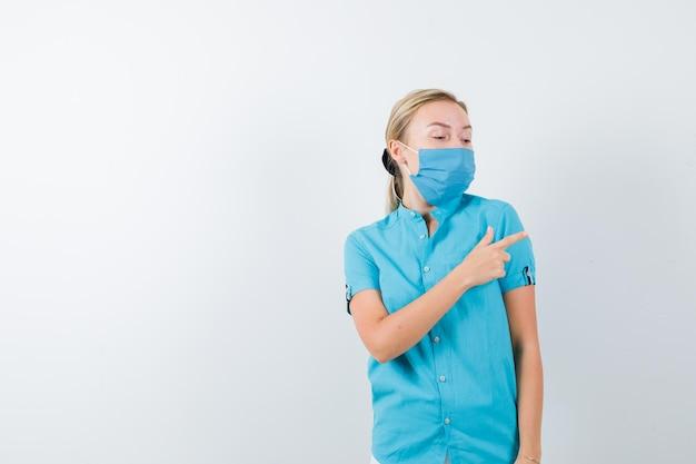 Junge blonde frau in freizeitkleidung, maske zeigt nach rechts, während sie wegschaut
