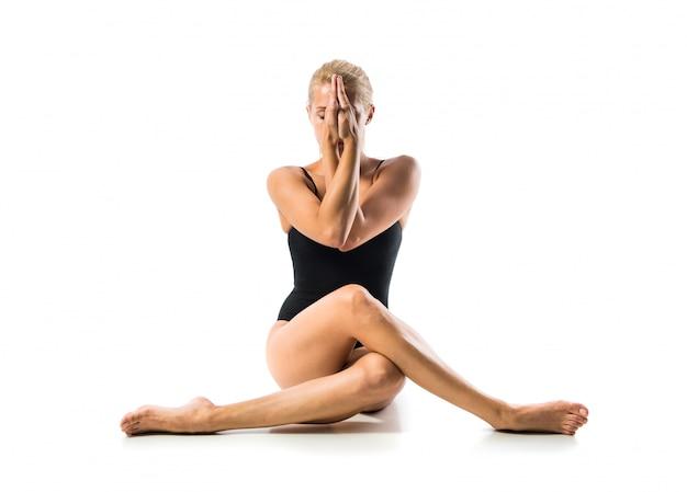 Junge blonde frau in maillot übender yogalektion