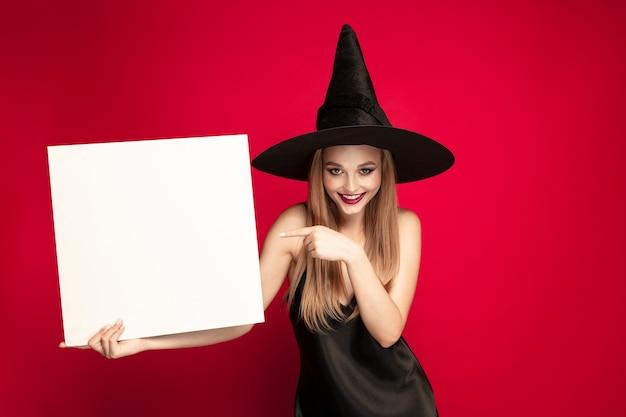 Junge blonde frau in schwarzem hut und kostüm auf rotem grund. attraktive kaukasische weibliche vorbildliche aufstellung. halloween, schwarzer freitag, cyber-montag, verkauf, herbstkonzept. exemplar. hält weiße platte.