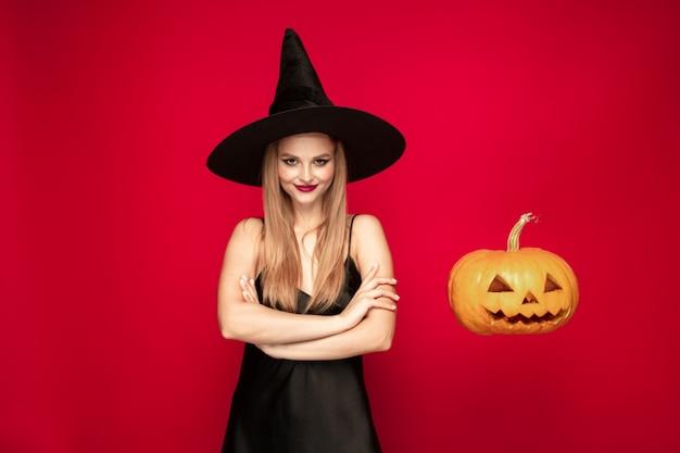 Junge blonde frau in schwarzem hut und kostüm auf rotem grund. attraktives kaukasisches weibliches modell. halloween, schwarzer freitag, cyber-montag, verkauf, herbstkonzept. exemplar. fliegender kürbis in der nähe.