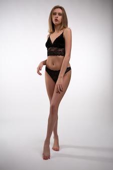 Junge blonde frau in schwarzer spitzenunterwäsche mit einer wunderschönen figur