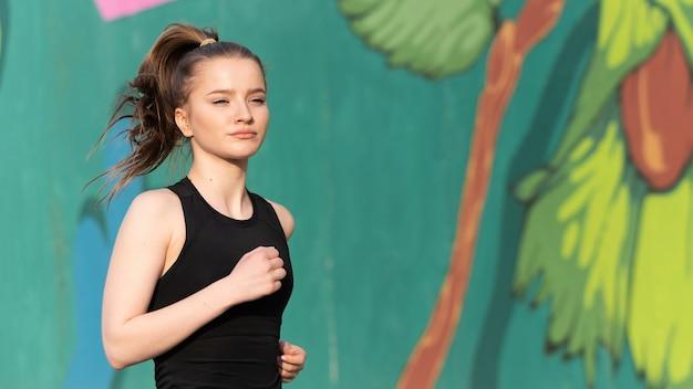 Junge blonde frau in sportbekleidung, die auf der straße beim training im freien, mehrfarbige wand auf dem hintergrund läuft