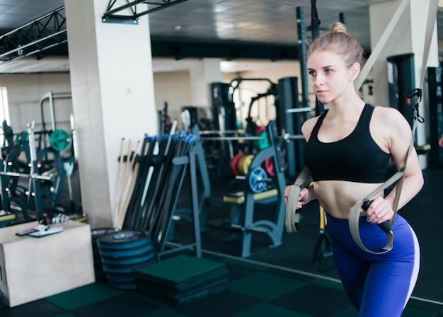 Junge blonde frau in sportbekleidung, die übung mit fitnessgurten in der turnhalle tut