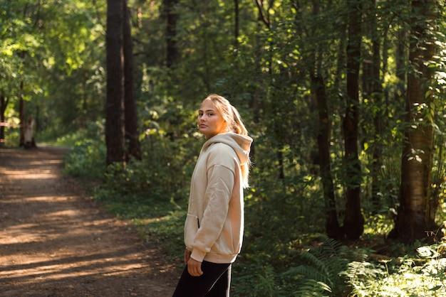 Junge blonde frau in sportkleidung hoodie im park