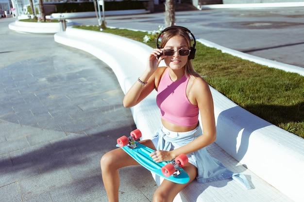 Junge blonde frau in stilvoller kleidung und sonnenbrille mit skateboard und kopfhörern im freien am sonnigen sommertag