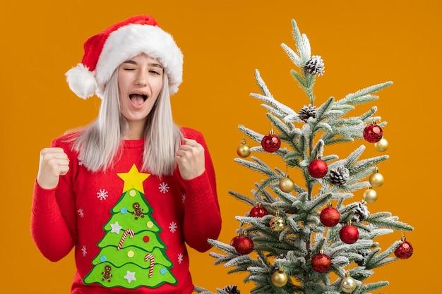 Junge blonde frau in weihnachtspullover und weihnachtsmütze ballt die fäuste glücklich und aufgeregt neben einem weihnachtsbaum über orangefarbener wand