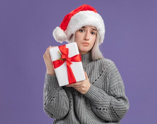 Junge blonde frau in winterpullover und weihnachtsmütze, die ein geschenk mit traurigem gesichtsausdruck über lila wand hält