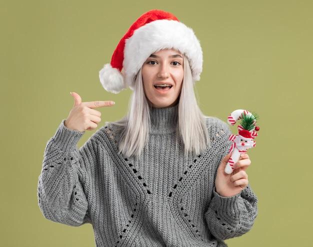 Junge blonde frau in winterpullover und weihnachtsmütze, die weihnachtszuckerstange hält und mit dem zeigefinger auf sich selbst zeigt, fröhlich lächelnd über grüner wand stehend