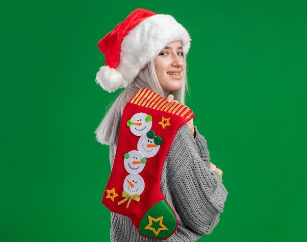 Junge blonde frau in winterpullover und weihnachtsmütze mit weihnachtsstrumpf auf ihrer schulter glücklich und freudig lächelnd über grünem hintergrund stehend