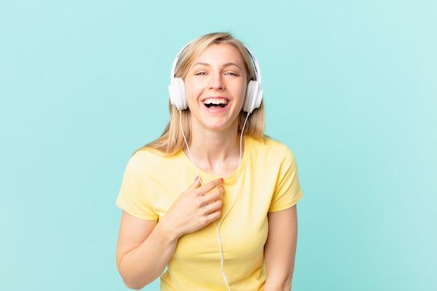 Junge blonde frau lacht laut über einen lustigen witz und hört musik.
