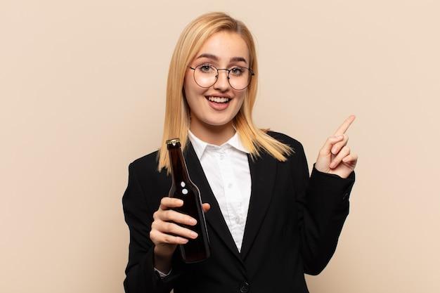 Junge blonde frau lacht, sieht glücklich, positiv und überrascht aus und verwirklicht eine großartige idee, die auf seitlichen kopierraum zeigt