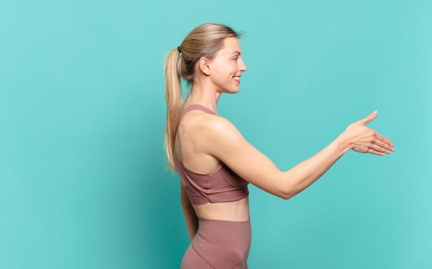 Junge blonde frau lächelt, begrüßt sie und bietet einen handschlag an, um ein erfolgreiches geschäft abzuschließen, kooperationskonzept. sportkonzept