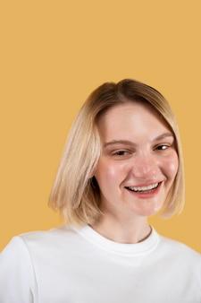 Junge blonde frau lächelt isoliert auf gelb