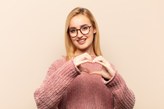 Junge blonde frau lächelt und fühlt sich glücklich, süß, romantisch und verliebt, herzform mit beiden händen machend