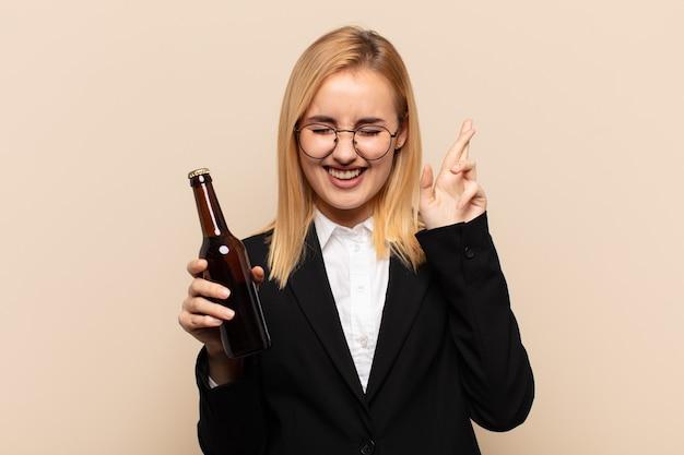 Junge blonde frau lächelt und kreuzt ängstlich beide finger, fühlt sich besorgt und wünscht oder hofft auf viel glück