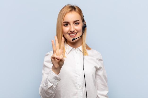 Junge blonde frau lächelt und sieht freundlich aus, zeigt nummer drei oder dritte mit der hand nach vorne und zählt herunter