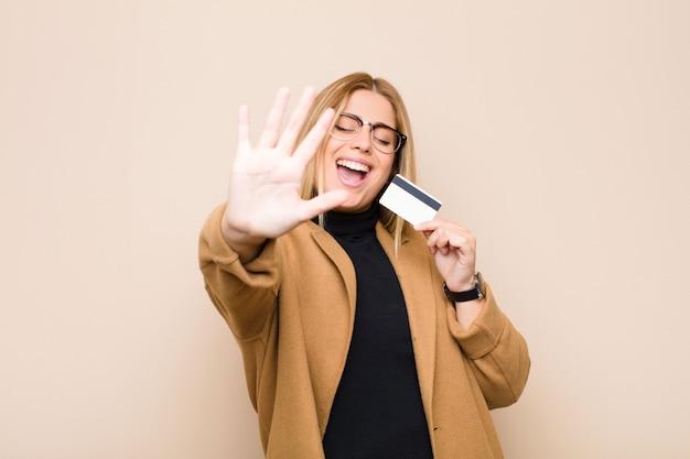 Junge blonde frau lächelt und sieht freundlich aus, zeigt nummer fünf oder fünfte mit der hand nach vorne, zählt mit einer kreditkarte herunter