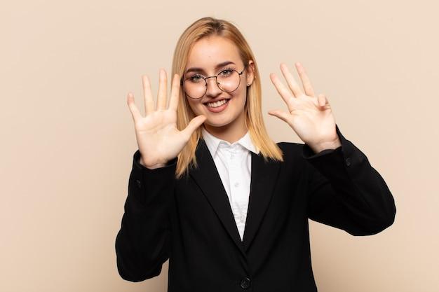 Junge blonde frau lächelt und sieht freundlich aus, zeigt nummer neun oder neun mit der hand nach vorne, countdown