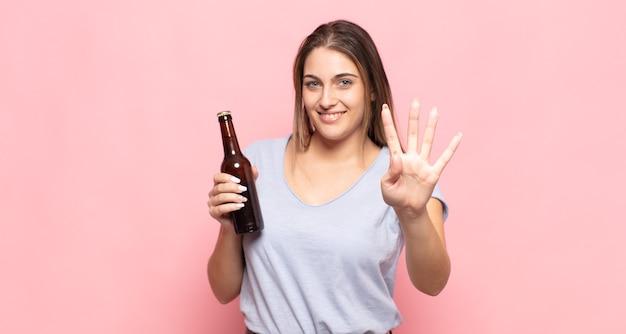 Junge blonde frau lächelt und sieht freundlich aus, zeigt nummer vier oder vierten mit der hand nach vorne, countdown