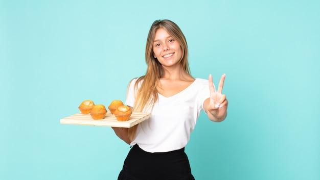 Junge blonde frau lächelt und sieht freundlich aus, zeigt nummer zwei und hält einen muffins-troy