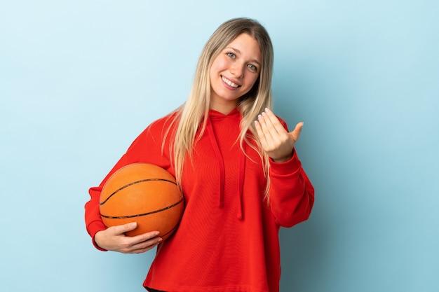 Junge blonde frau lokalisiert auf blau, das basketball spielt und kommende geste tut