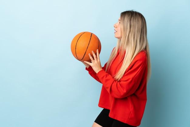 Junge blonde frau lokalisiert auf blau spielendem basketball