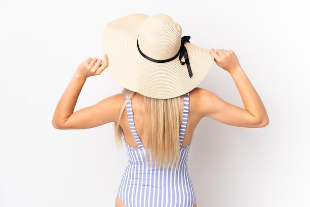 Junge blonde frau lokalisiert auf weißer wand im badeanzug und in der hinteren position