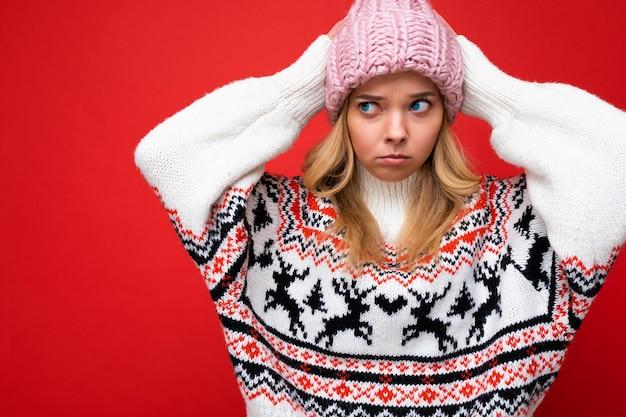 Junge blonde frau lokalisiert über roter hintergrundwand, die winterpullover und rosa hut trägt, der zur seite schaut.