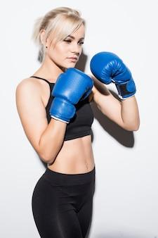 Junge blonde frau mit blauen boxhandschuhen bereit, auf weiß zu kämpfen