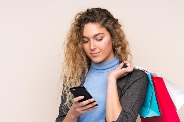 Junge blonde frau mit dem gelockten haar lokalisiert auf beige wand, die einkaufstaschen hält und eine nachricht mit ihrem handy an einen freund schreibt
