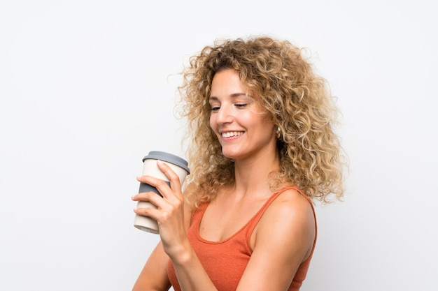 Junge blonde frau mit dem lockigen haar, das einen mitnehmerkaffee anhält