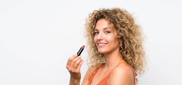 Junge blonde frau mit dem lockigen haar, das roten lippenstift anhält
