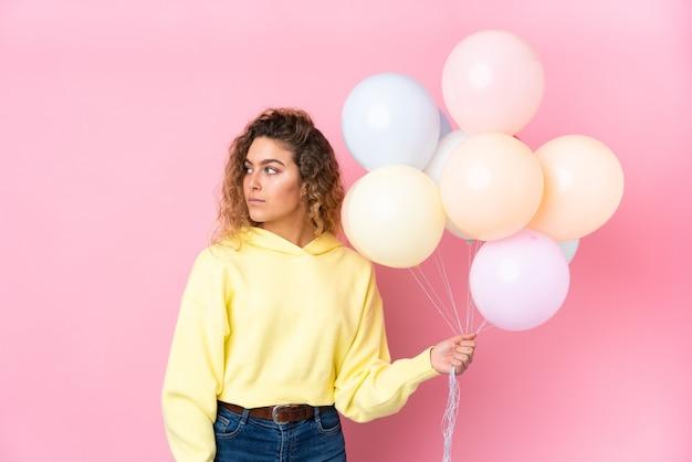 Junge blonde frau mit dem lockigen haar, das viele luftballons fängt, die auf rosa schauender seite lokalisiert werden