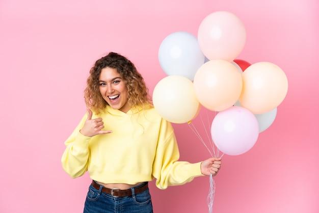 Junge blonde frau mit dem lockigen haar, das viele luftballons fängt, die auf rosa wand lokalisiert werden, die telefongeste macht