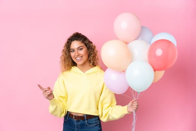 Junge blonde frau mit dem lockigen haar, das viele luftballons fängt, die auf rosa zeigefinger zur seite lokalisiert werden