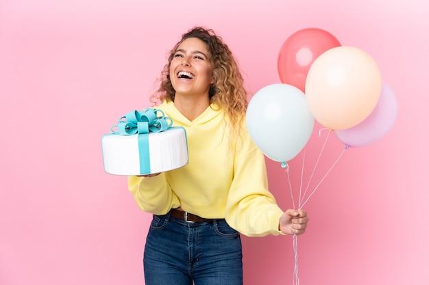 Junge blonde frau mit dem lockigen haar, das viele luftballons fängt und einen großen kuchen hält, der auf rosa wand lokalisiert wird