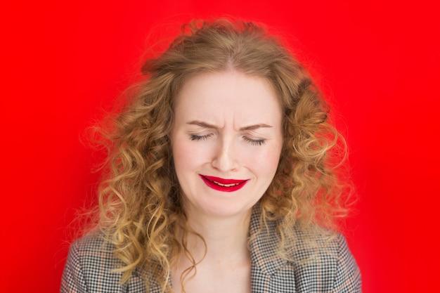 Junge blonde frau mit den grünen augen, die über rote oberfläche weinen